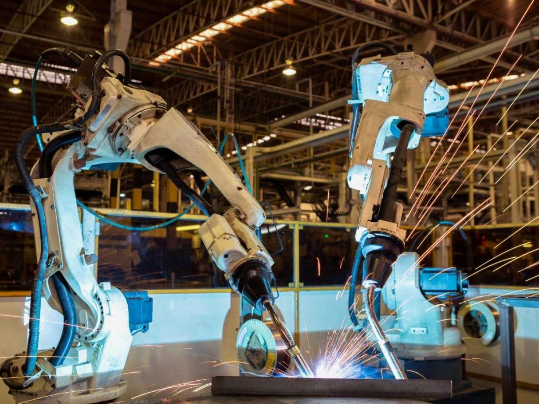 Robots welding in auto factory